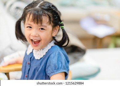 Happy smiley face.Cute asian girl 4-5 year old ready for dinner at home.Joyful portrait of asian elementary school student.