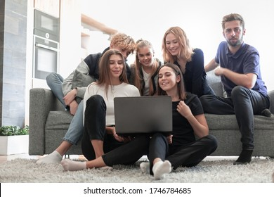 Happy smilimg young peple on sofa at home using laptop computer