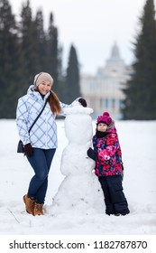 Happy and smiling adult woman and young girl standing near snowman on wintry field of park, wintertime