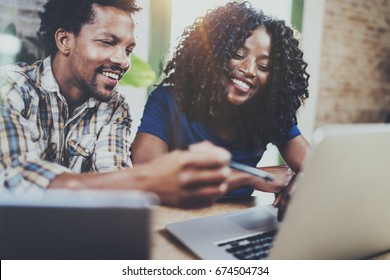 Happy smiling african american couple working together at home.Young black man and his girlfriend using laptop at home in the living room. Horizontal,blurred background.Flare
