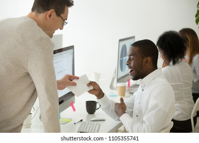 Happy smiling African American employee excited by unexpected money bonus in envelope, black person rewarded for high work results, praised for successful project completion. Achievement concept