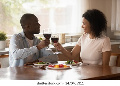 Happy smiling african american family couple sitting at dinner table in kitchen, holding glasses of wine, cheering, toasting, celebrating wedding anniversary or special event, romantic dating concept.