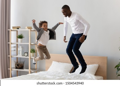 Happy smiling African American father and little son jumping on bed, laughing dad playing with excited adorable preschool child in bedroom, funny family activity at home, having fun on weekend
