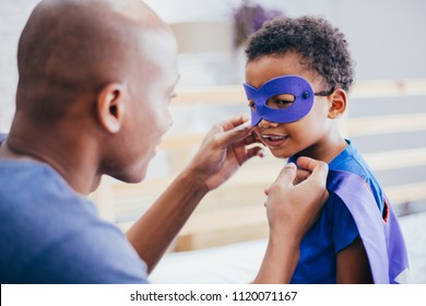 Happy smiling African American son being supported and helped by supportive father for little adventure and protection