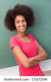 happy smiling African American woman with a frizzy afro hairstyle and a beautiful friendly smile standing with folded arms against a green blackboard