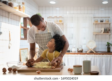 Happy Smiling African family  in Aprons Cooking and kneading dough on wooden table. Black Father with son in yellow shirt baking cake together and looking at Each Other in white home kitchen interior.