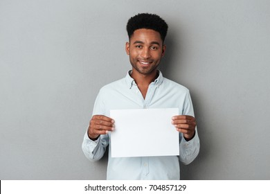 Happy smiling african man holding blank sheet of paper while standing isolated over gray background