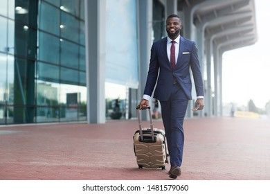 Happy smiling african man in suit with luggage leaving airport