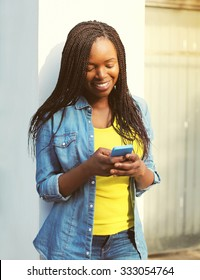 Happy smiling african woman holding phone in city