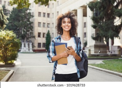 Happy smiling african-american student girl with backpack at university background. Woman with mobile and workbooks having rest in campus during lunch break. Technology, education, leisure concept