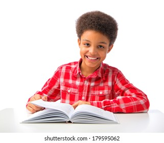 Happy smiling Afro-American school boy studying, reading book. Isolated, over white background, with copy space