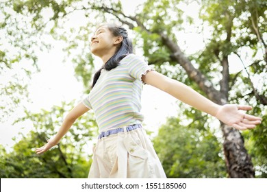 Happy smiling asian child girl standing with arms outstretched in green nature,female teenage enjoy breathing fresh air with raised arms up and closed eyes having fun,relax in park,healthy lifestyle