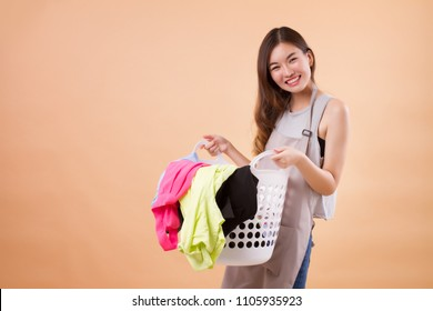 happy smiling asian chinese woman carrying laundry cloth basket; portrait of girl domestic helper, woman housekeeper, housewife, woman maid holds laundry cloth basket; asian young adult woman model