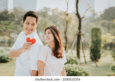 Happy smiling Asian couple in love holding heart at park in the morning