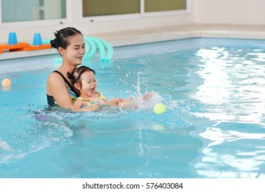 happy smiling asian little girl with mother swimming at water pool