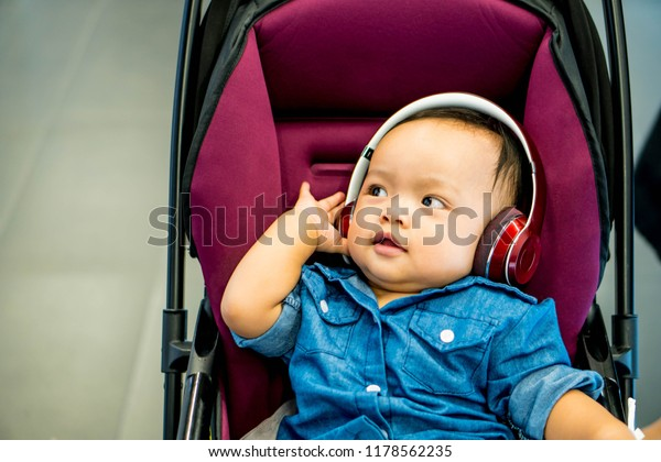 Happy smiling asian newborn cute baby infant sitting stroller listens lullaby songs and music in headphones cheerful children's portrait baby girl 8 months of age with happy expression