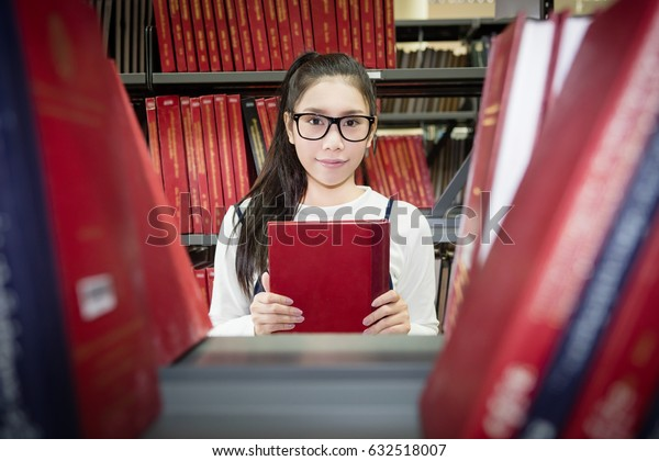 Happy smiling Asian student choosing books with bookshelves in library