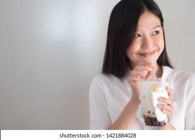 Happy smiling asian woman drinking iced bubble milk tea; aka boba tea, pearl milk tea, tapioca tea; Asian exotic beverage concept