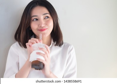 Happy smiling asian woman drinking iced bubble milk tea; aka boba tea, pearl milk tea, tapioca tea, asian exotic beverage concept; retouched image