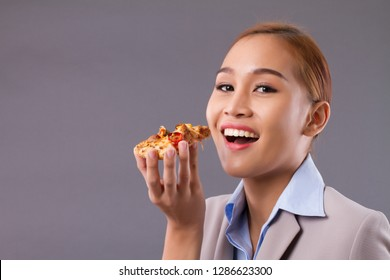 Happy smiling Asian woman eating pizza; Portrait of south east Asian woman holding delicious italian pizza; enjoy eating pizza concept; Asian young adult, tan skin woman model