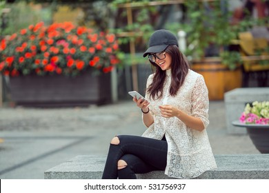 Happy smiling asian woman or hipster student portrait with smartphone sitting on bench on the city street with trees and flowers. Mixed race Asian Chinese Caucasian elegant beautiful female model.
