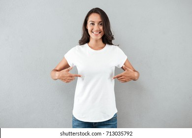 Happy smiling asian woman pointing with two fingers on her blank white t-shirt while standing isolated over gray background