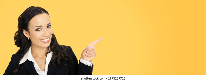Happy smiling attractive woman in black confident suit, pointing showing advertising copy space area. Business concept. Orange yellow colour background. Brunette businesswoman. Wide banner image.