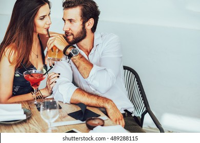 Happy smiling attractive young couple on date sitting in street cafe in summer, sharing drink, looking at each other with love, flirting, having fun together