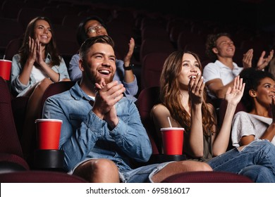 Happy smiling audience clapping hands while sitting at the cinema and watching movie