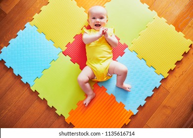 Happy smiling baby girl lying on colorful play mat on the floor
