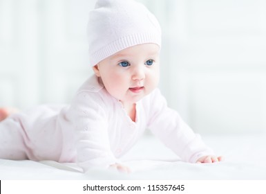 Happy smiling baby girl in a pink knitted hat