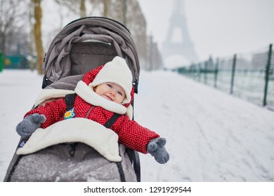 Happy smiling baby girl in stroller near the Eiffel tower on a day with heavy snow. Little kid enjoying the very first snow. Unusual weather conditions in Paris.
