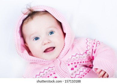 Happy smiling baby girl wearing a warm knitted jacket with heart ornament