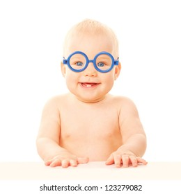 Happy smiling baby in glasses sitting in the classroom at school desk. Two baby teeth in the mouth. Isolated on white background