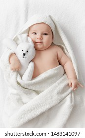 Happy smiling baby in a towel after bathing