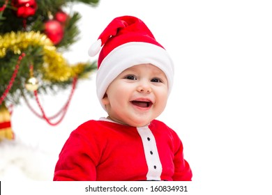 Happy smiling baby wearing a red and white Christmas Santa hat and suit, isolated on a white background.