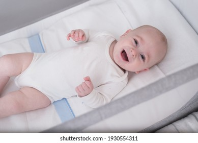 happy and smiling baby wearing white clothes lying in a crib. Baby smiles at his mother