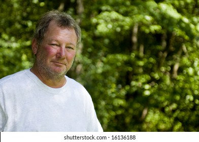 happy smiling baby-boomer middle age man wooded backyard background unshaven with beard stubble