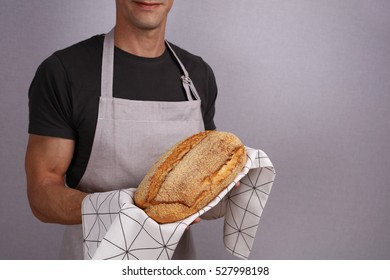 Happy smiling Baker holding loaf of tasty fresh bread. Gluten free cornbread