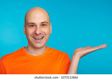Happy smiling bald man presenting some product. Handsome guy in orange shirt isolated over bright blue background