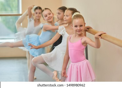 Happy smiling ballerina in pink suit. Adorable little ballet girl standing at ballet barre in studio and looking at camera.