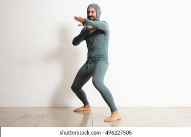 Happy smiling bearded fitted male wearing snowboarding thermal baselayer suite from merino wool and acts like a ninja in defend position, isolated on white