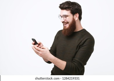 Happy  smiling bearded guy is uiding a phone over white background