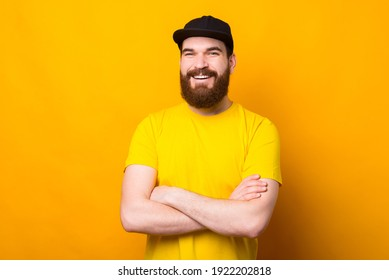 Happy smiling bearded hipster man in yellow shirt standing with crossed arms