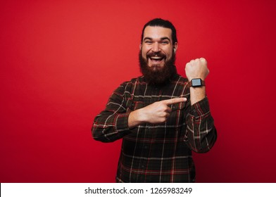 Happy smiling bearded man is poiting at his smartwatch