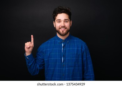 Happy smiling bearded young man looking at camer and pointing up with finger over dark background