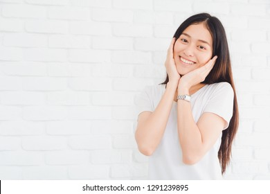 Happy smiling beautiful Asian woman gesturing with hands and showing two hands touch on her face in a white brick wall background.Concept of healthy and beauty lifestyle girl.