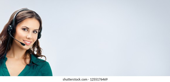Happy smiling beautiful female phone operator in green confident clothing, empty copy space place for slogan or some advertising text message, over grey background. Call center and support concept.