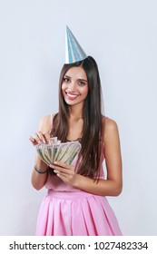 Happy smiling beautiful girl in birthday hat and pink dress holding dollar money