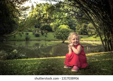 Happy smiling beautiful kid girl on grass in lush green summer park in tree shadow happy carefree childhood lifestyle